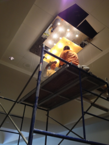 Workers install electrical lighting